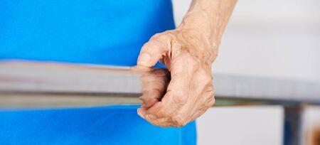 terapia ocupacional: arrugada mano de la mujer mayor en el mango de una cinta de correr en fisioterapia
