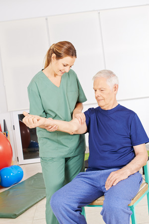pangs: Old man sitting with shoulder pain in physical therapy Stock Photo