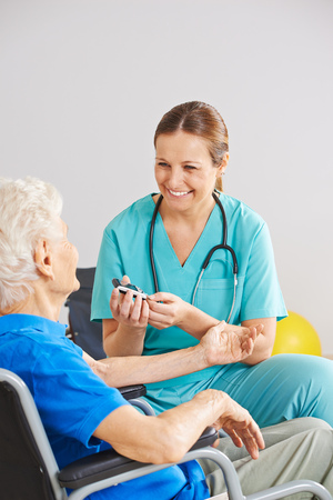 Geriatric caregiver doing blood sugar monitorin for old diabetes patient Stock Photo
