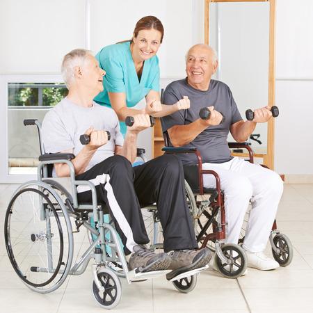 persona en silla de ruedas: Fisioterapeuta con dos hombres mayores en sillas de ruedas levantamiento de pesas Foto de archivo