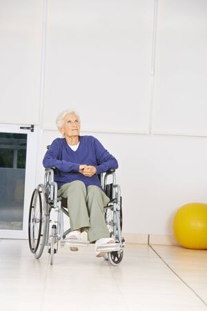 eldercare: Old pensive woman sitting in wheelchair and looking up in a nursing home