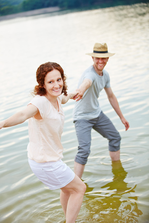 Laughing young couple playing in water of lake in summer Stock Photo