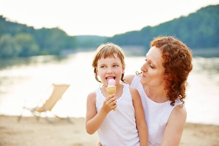 lake beach: Girl eating ice cream with mother in summer on beach of a lake