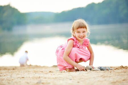 lake beach: Happy girl playing on beach of lake in summer