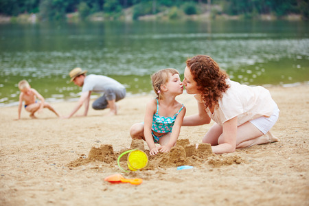 mother love: Girl kissing mother while playing on beach in summer vacation
