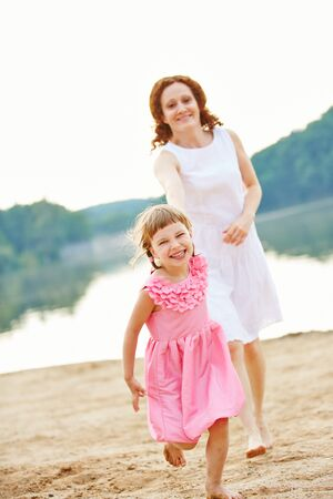 lake beach: Mother and daughter running over beach of lake in summer Stock Photo