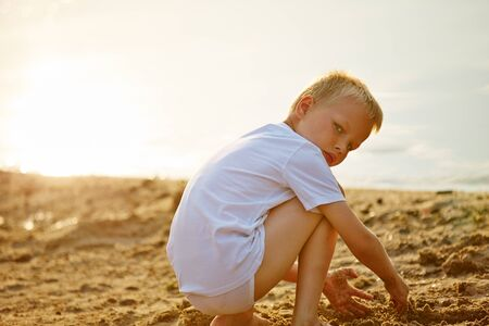 sandpit: Boy playing with his hands in the sand on a beach in summer