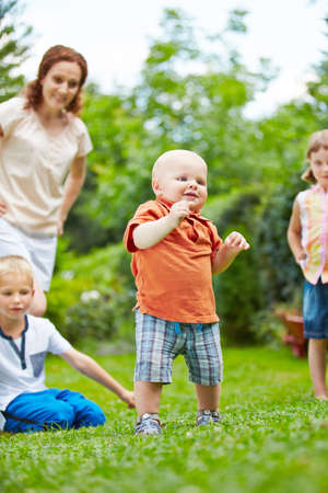 mum and child: Proud baby learning first steps in garden in summer with family watching