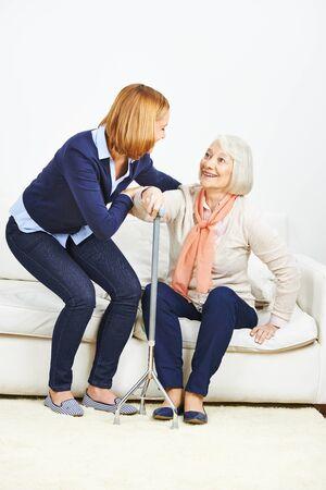 levantandose: Mujer ayudar a la mujer mayor con el bastón de levantarse de un sofá