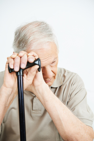 retired man: Old man with depression putting his hands on a cane