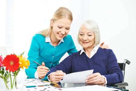 caring for: Caring for senior woman with wheelchair in family with granddaughter Stock Photo
