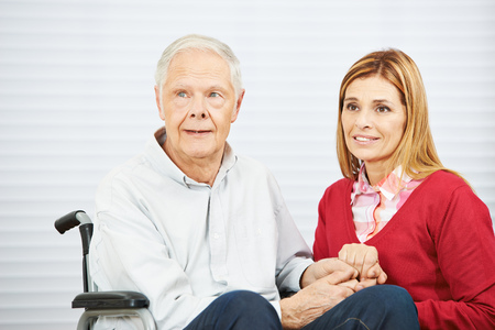 mobility nursing: Senior man in wheelchair and daughter holding hands in a nursing home