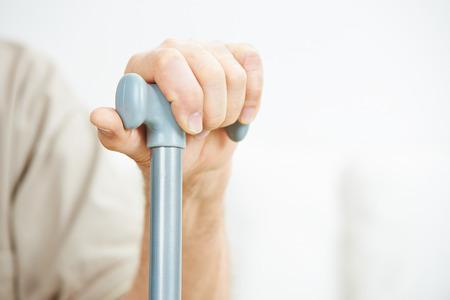 La mano del hombre mayor que se aferra a un bastón