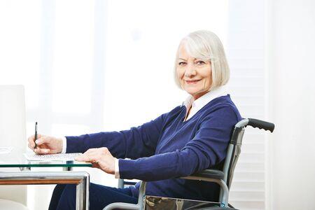 testament schreiben: Lächelnde ältere Frau im Rollstuhl auf einem Tisch Gedächtnistraining tun Lizenzfreie Bilder