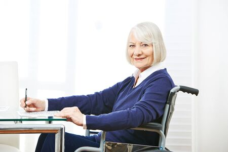 nursing allowance: Smiling senior woman in wheelchair on a table doing memory training Stock Photo