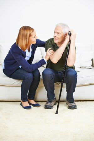 house call: Caregiver talking to senior man at home on a sofa