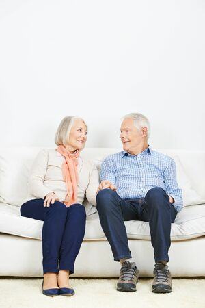 man sit: Communication between senior couple at home on a sofa