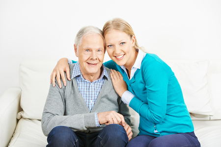 eldercare: Young happy woman embracing old senior man