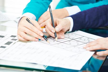 Las manos con la solución del sudoku lápiz de memoria como la formación