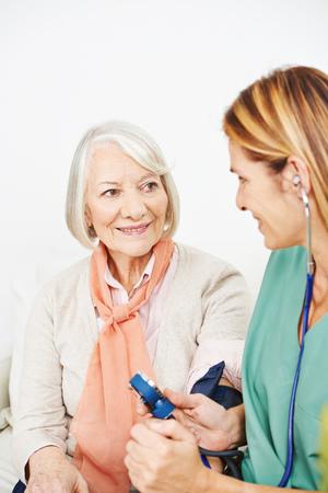 senior home: Nurse monitoring blood pressure for senior woman in nursing home