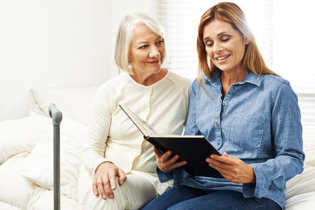 house call: Old woman and daughter looking at photo album together at home