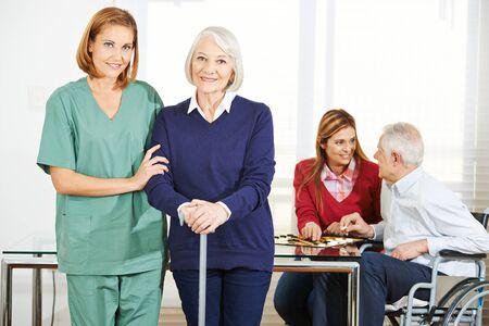 Caregiver travailler avec les gens heureux supérieurs dans la maison de soins infirmiers Banque d'images