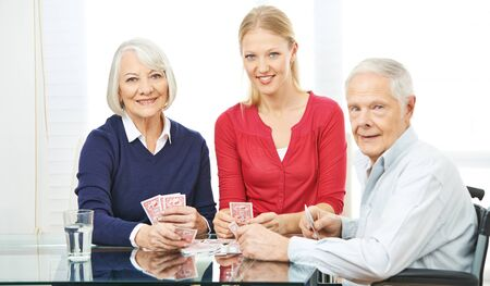 social work aged care: Happy family with senior people playing cards at home