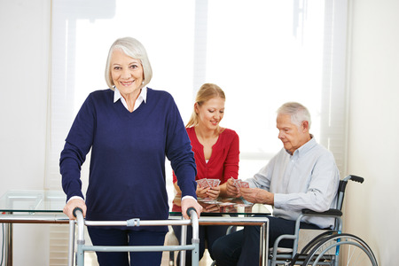 eldercare: Family generations at home playing cards at table Stock Photo