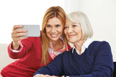 house call: Young and old woman taking selfie together with a smartphone Stock Photo