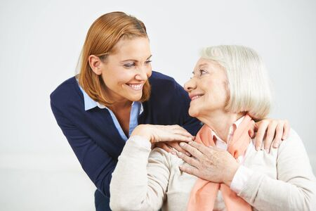 house call: Happy senior woman and daughter smiling at each other Stock Photo
