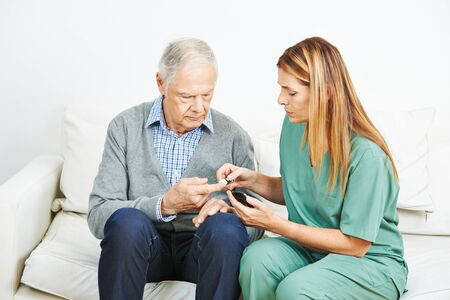 senior citizens: Blood glucose monitoring for senior man with diabetes in nursing home
