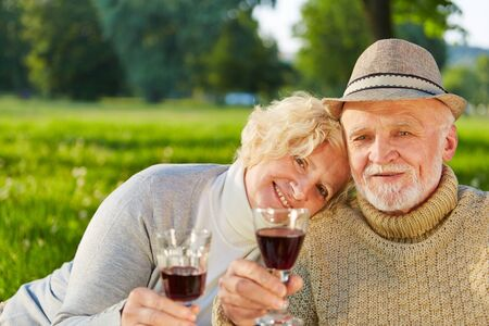 lady in red: Happy senior couple drinking red wine in a garden in fall