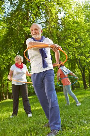 Gruppo maggiore con cerchi in una classe di fitness che esercitano in natura in un giardino Archivio Fotografico