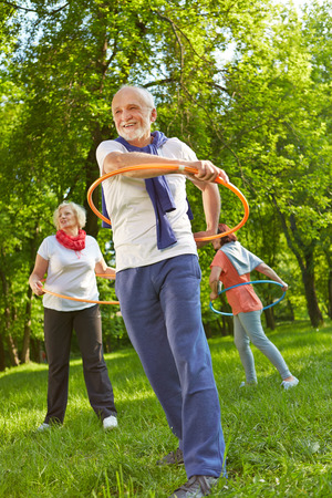 seniors: Senior group with hoops in a fitness class exercising in nature in a garden