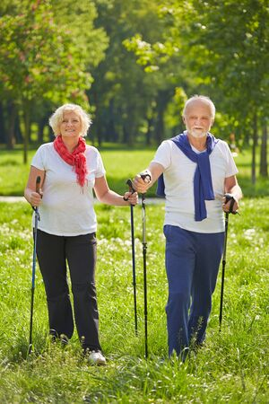 Happy senior couple doing Nordic Walking in summer in nature
