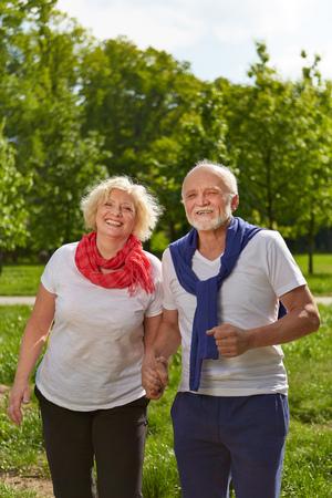senior women: Happy Senior couple holding hands in a green park Stock Photo