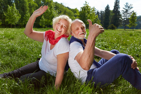 green thumb: Smiling happy senior couple in summer vacation waving hands and holding thumbs up