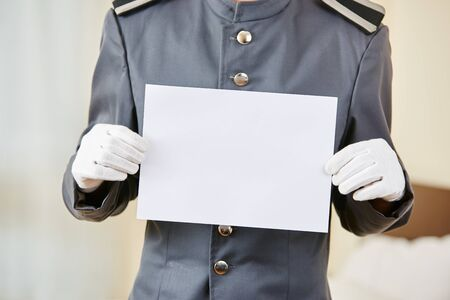 hotel staff: Hotel clerk holding empty white sheet of paper in hotel room