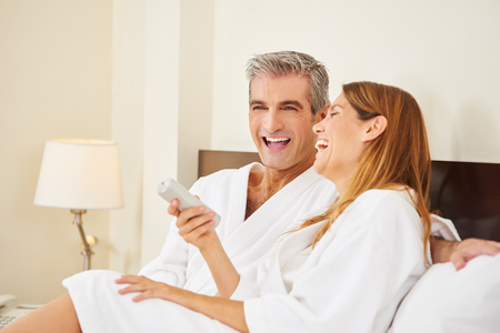 Happy couple laughing during holiday stay in hotel room