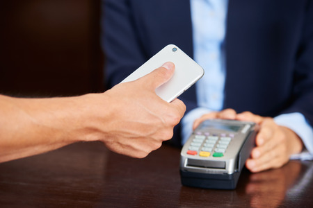 hotel staff: Guest paying bill with his smartphone at the hotel reception Stock Photo