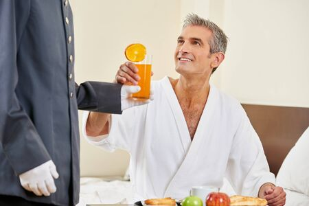 breakfast room: Room service bringing breakfast with orange juice to a hotel room guest