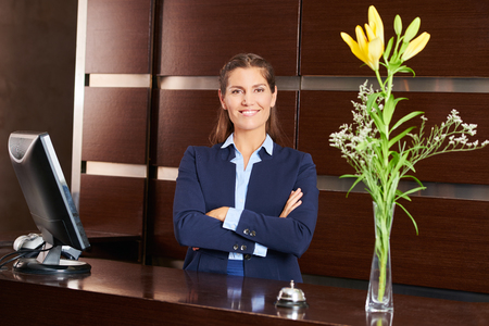 hospitality staff: Smiling woman as receptionist in a hotel lobby