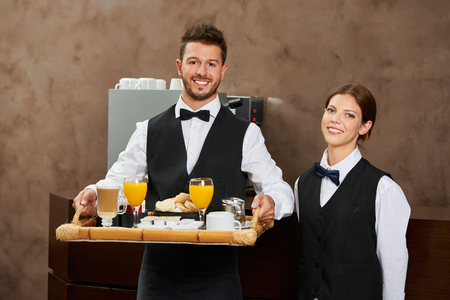 hotel staff: Waiter staff team serving breakfast in a hotel restaurant