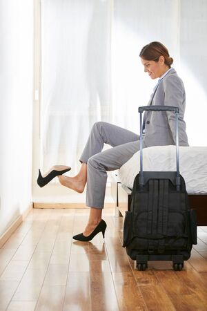 shoes off: Business woman in hotel room with suitcase taking off her shoes