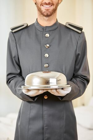 hotel staff: Friendly hotel page with food under cloche in a hotel room