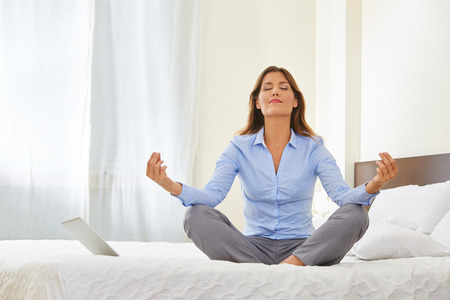 Business woman doing yoga on a bed in a hotel room