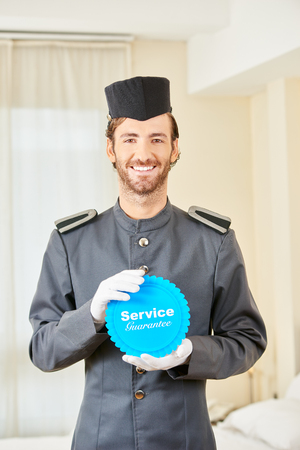 hospitality staff: Happy page holding badge with service guarantee in a hotel room Stock Photo