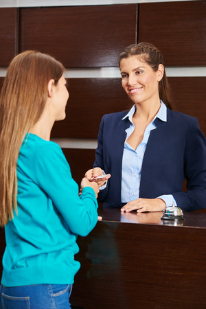 hospitality staff: Woman at hotel reception giving key card to female guest during check-in