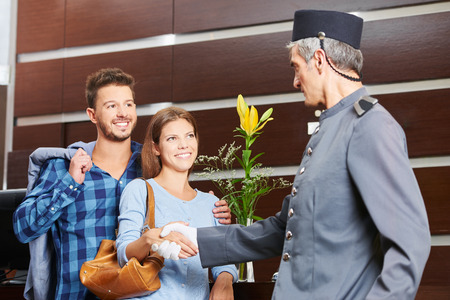 arrive: Concierge giving handshake to couple in hotel as welcome sign