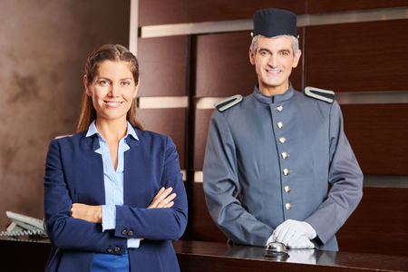hospitality staff: Happy concierge and smiling receptionist in a hotel as team in uniform